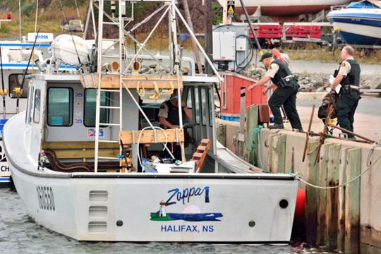 Fisheries officers are shown boarding the Zappa 1 in Ballantyne's Cove on Oct. 8, 2014. (Submitted to CBC)